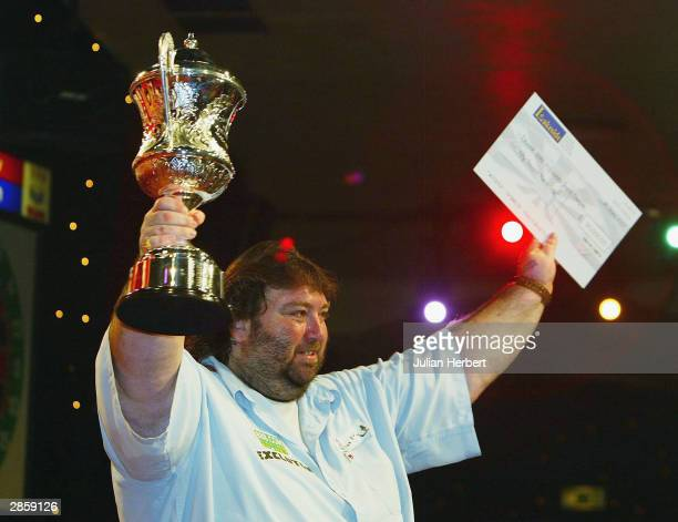 Andy Fordham of England holds the trophy and winner's cheque after beating Mervyn King in the final of The BDO Lakeside World Darts Championships at...