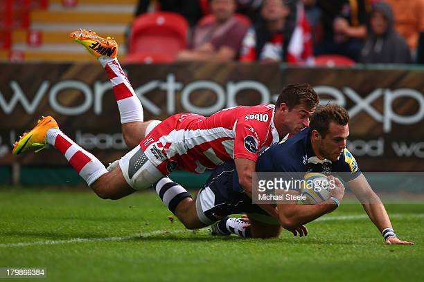 Andy Forsyth of Sale Sharks scores his sides second try despite the efforts of Henry Trinder of Gloucester during the Aviva Premiership match between...
