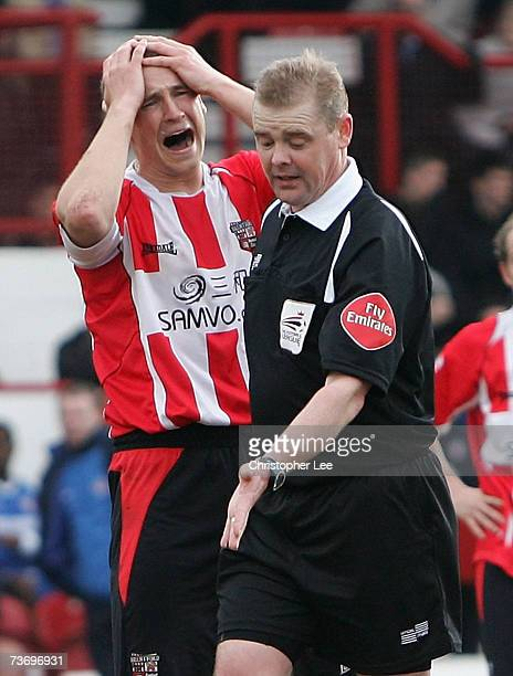 Andy Frampton of Brentford holds his head after referee A Hall gives a penalty in injury time during the CocaCola League One match between Brentford...