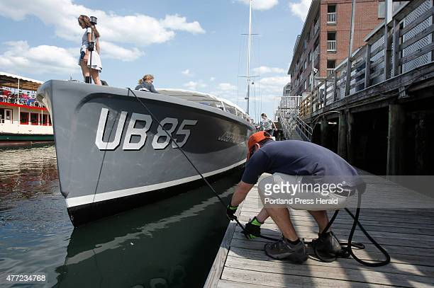 Andy Gildart ties up the Joseph S. Kennedy, a UB85 Navy boat, while Nicole Frantz, left, and her mother Cathleen Hart-Frantz explore the bow of the...