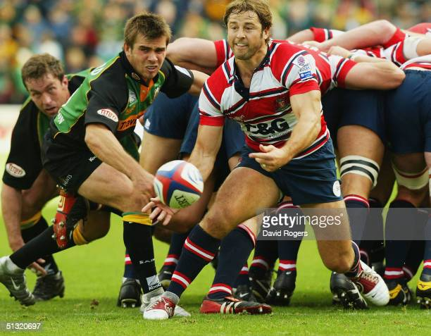 Andy Gomarsall of Gloucester passes the ball as Johnny Howard tries to intercept during the Zurich Premiership match between Northampton Saints and...