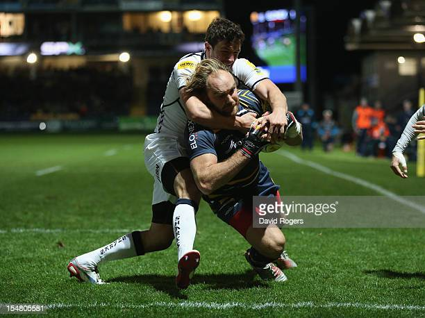 Andy Goode of Worcester dives over for a try despite being held by Tom Brady during the Aviva Premiership match between Worcester Warriors and Sale...
