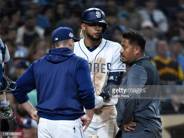 Andy Green of the San Diego Padres and a trainer talk with Fernando Tatis Jr #23 during the sixth inning of a baseball game against the Tampa Bay...