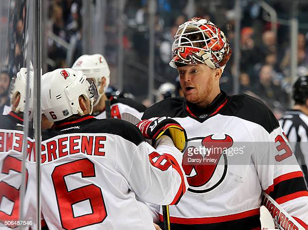 Andy Greene and goaltender Cory Schneider of the New Jersey Devils discuss strategy during a first period stoppage in play against the Winnipeg Jets...