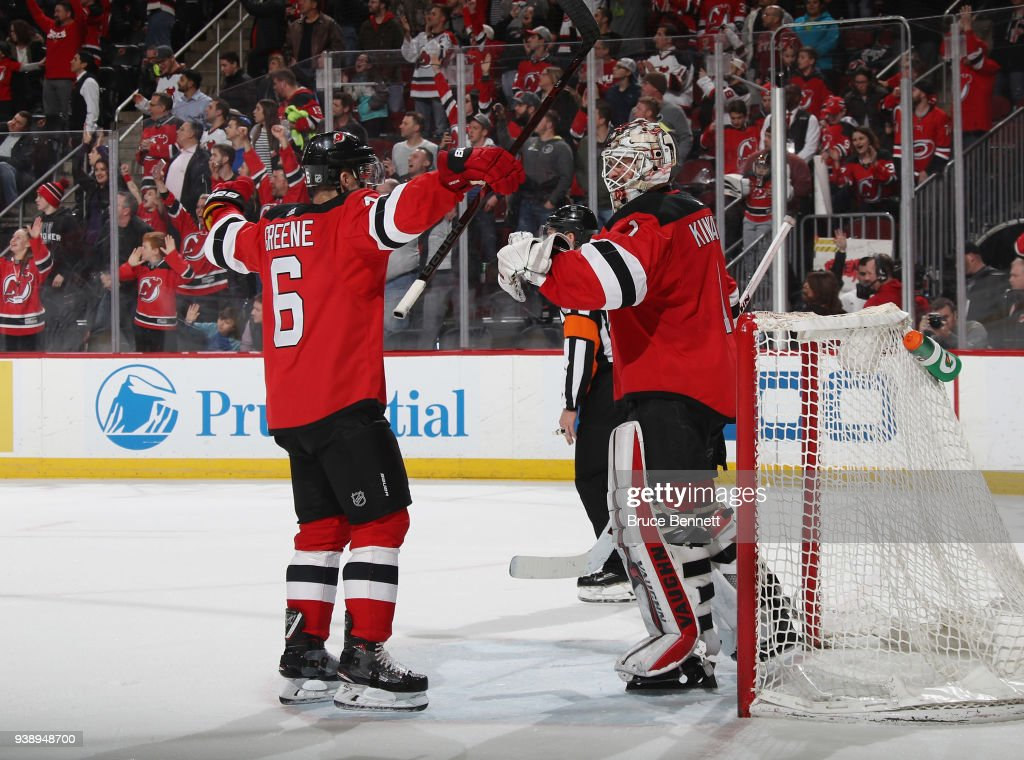 Andy Greene #6 and Keith Kinkaid #1 of the New Jersey Devils celebrate their 4-3 victory over the Carolina Hurricanes at the Prudential Center on March 27, 2018 in Newark, New Jersey.