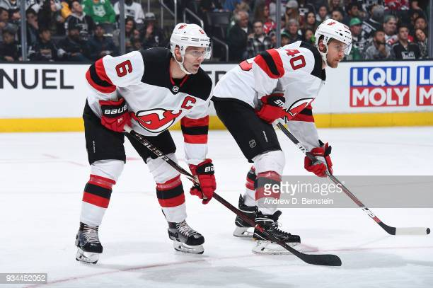 Andy Greene and Michael Grabner of the New Jersey Devils await a faceoff during a game against the Los Angeles Kings at STAPLES Center on March 17...