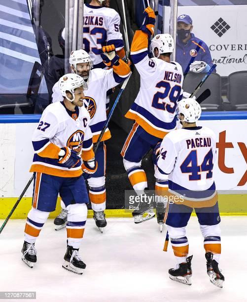 Andy Greene, Anders Lee, Brock Nelson and Jean-Gabriel Pageau of the New York Islanders of the New York Islanders celebrate their teams 4-0 victory...