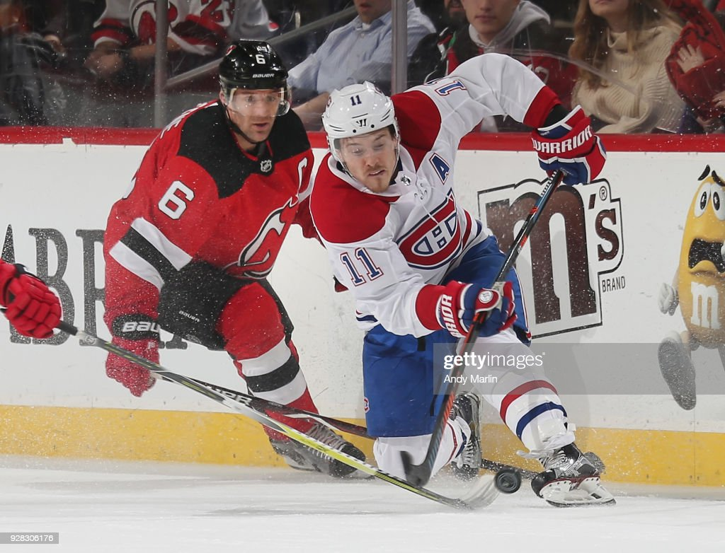 Andy Greene #6 of the New Jersey Devils and Brendan Gallagher #11 of the Montreal Canadiens battle for a loose puck during the game at Prudential Center on March 6, 2018 in Newark, New Jersey.