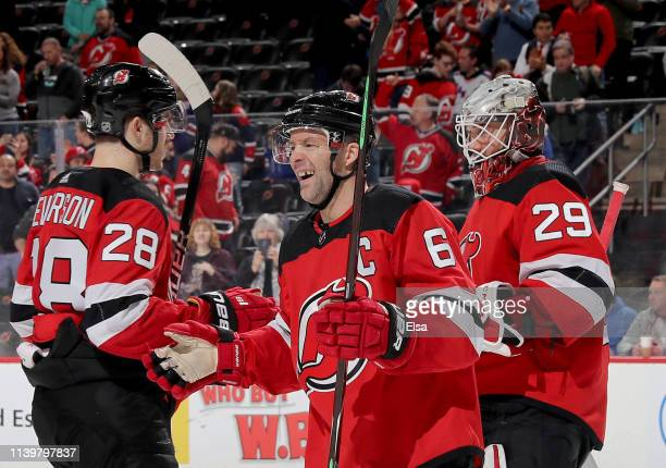 Andy Greene of the New Jersey Devils celebrates the win with teammates Damon Severson and Mackenzie Blackwood after the win over the New York Rangers...