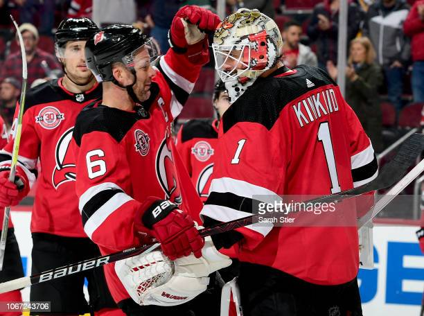 Andy Greene of the New Jersey Devils congratulates teammate Keith Kinkaid after the 42 win over the Pittsburgh Penguins at Prudential Center on...