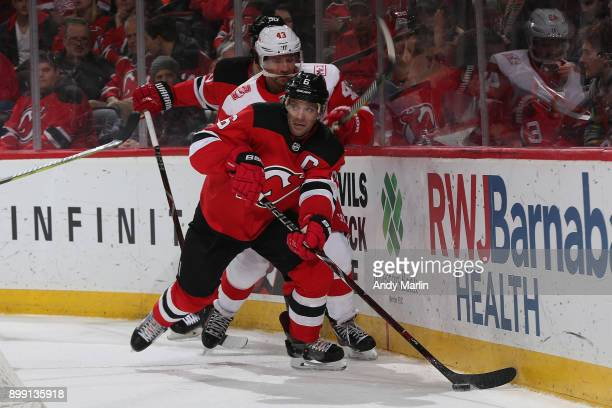 Andy Greene of the New Jersey Devils controls the puck in front Darren Helm of the Detroit Red Wings during the game at Prudential Center on December...