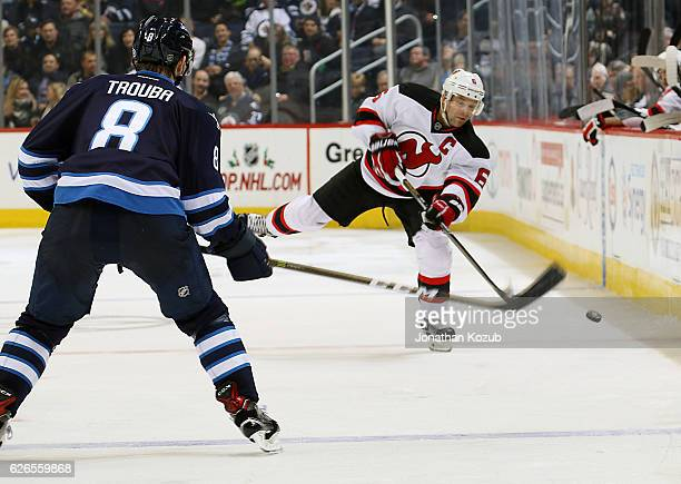 Andy Greene of the New Jersey Devils shoots the puck down the ice as Jacob Trouba of the Winnipeg Jets looks on during third period action at the MTS...