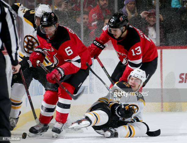 Andy Greene of the New Jersey Devils takes the puck from David Pastrnak of the Boston Bruins as teammate Nico Hischier defends on November 22 2017 at...