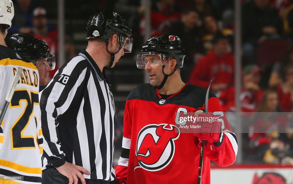 Andy Greene #6 of the New Jersey Devils talks with linesman Brian Mach #78 during the game against the Boston Bruins at Prudential Center on February 11, 2018 in Newark, New Jersey.