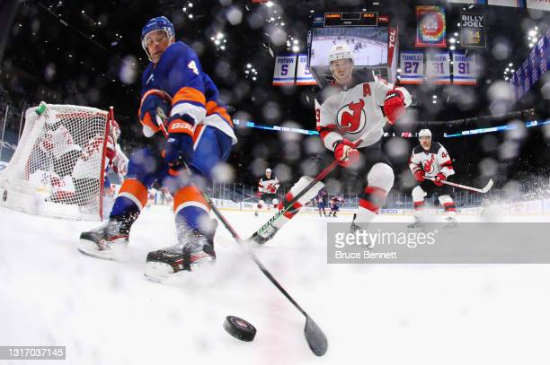 Andy Greene of the New York Islanders and Damon Severson of the New Jersey Devils pursue the puck at the Nassau Coliseum on May 08, 2021 in...