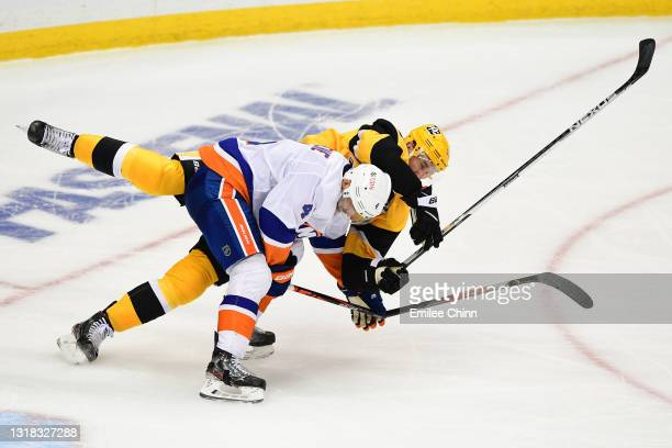 Andy Greene of the New York Islanders is called for interference against Jeff Carter of the Pittsburgh Penguins during the second period in Game One...