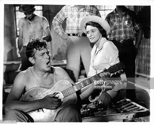 Andy Griffith playing guitar as Patricia Neal watches in a scene from the film 'A Face In The Crowd', 1957.