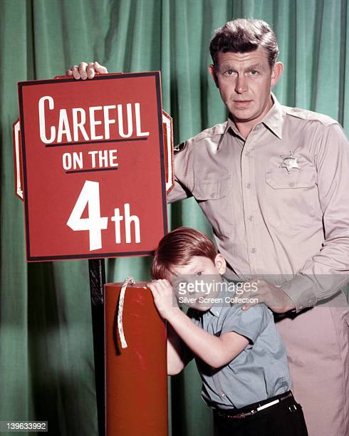 Andy Griffith US actor and Ron Howard US actor pose beside a large firework with a sign reading 'Careful on the 4th' in a publicity portrait issued...
