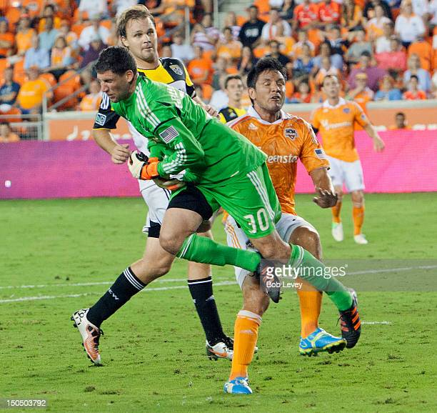 Andy Gruenebaum of the Columbus Crew and Brian Ching of the Houston Dynamo collide during the second half at BBVA Compass Stadium on August 19 2012...