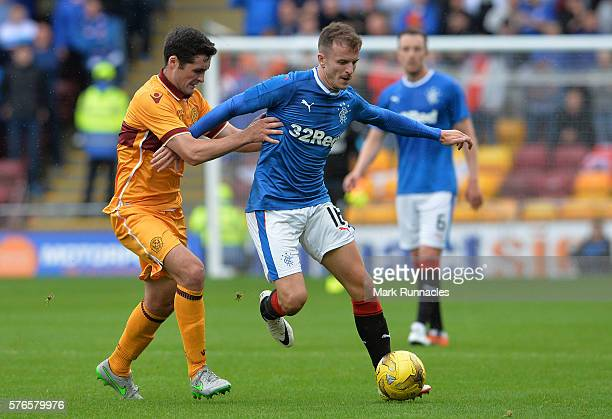 Andy Halliday of Rangers is tackled by Carl McHugh of Motherwell during the Scottish League Cup First Round Group Stage match between Motherwell FC...