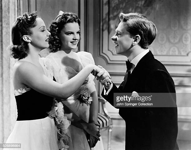 Andy Hardy takes the hand of Daphne Fowler as Betsy Booth watches in the 1940 film Andy Hardy Meets Debutante