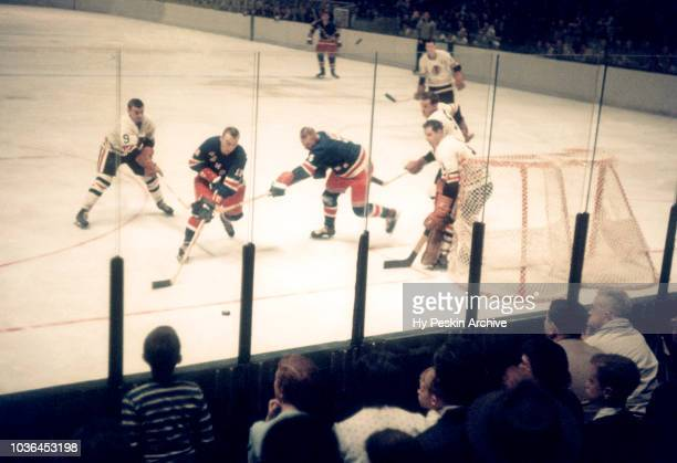 Andy Hebenton of the New York Rangers goes after the puck as goalie Glenn Hall and Nick Miskoski of the Chicago Blackhawks defend the net during an...
