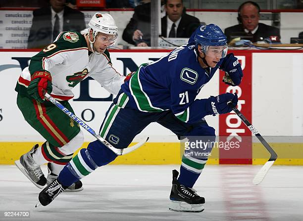Andy Hilbert of the Minnesota Wild and Mason Raymond of the Vancouver Canucks skate up ice during their game at General Motors Place on October 17...