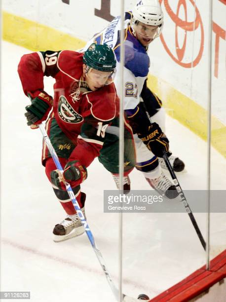 Andy Hilbert of the Minnesota Wild tries to keep the puck away from Alex Pietrangelo of the St Louis Blues at the Xcel Energy Center on September 24...
