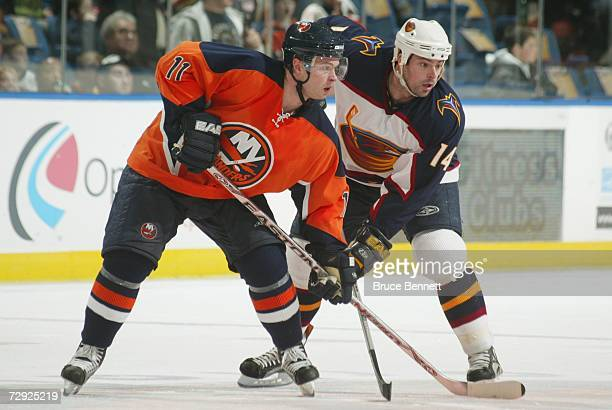 Andy Hilbert of the New York Islanders and Jon Sim of the Atlanta Thrashers gets set on a face off during the NHL game on December 16 2006 at the...