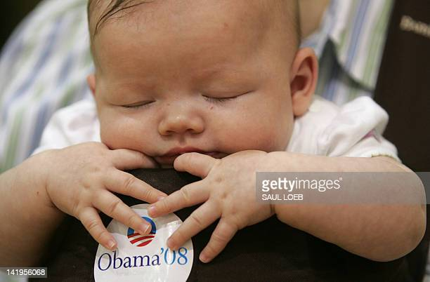 Andy Hunsinger of Newton Iowa holds his 3monthold son Avary as they listen to Democratic presidential hopeful and Illinois Senator Barack Obama speak...