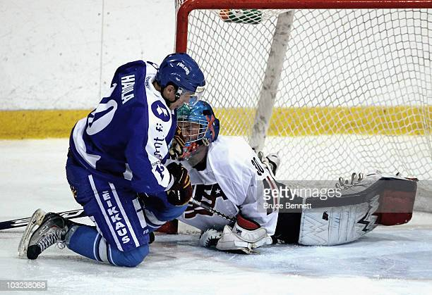 Andy Iles of Team USA makes the stop on Erik Haula of Team Finland at the USA Hockey National Evaluation Camp on August 4, 2010 in Lake Placid, New...