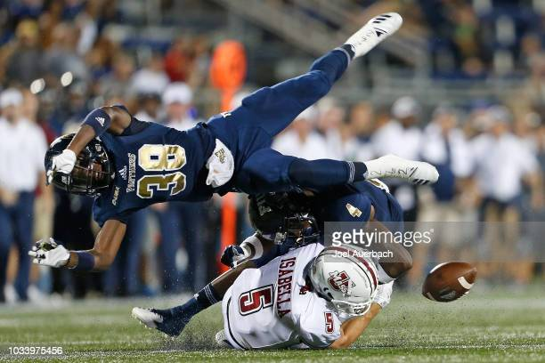 Andy Isabella of the UMass Minutemen is unable to hold onto the ball after being hit by Richard Dames of the Florida International Panthers at FIU...