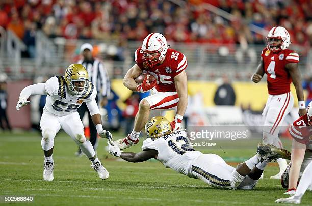 Andy Janovich of the Nebraska Cornhuskers jumps over Jayon Brown of the UCLA Bruins during the Foster Farms Bowl at Levi's Stadium on December 26...