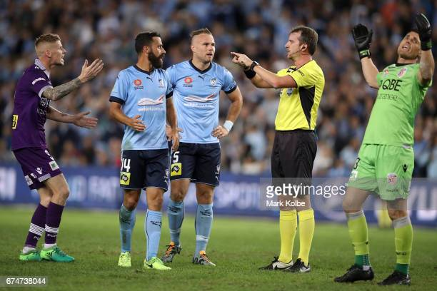 Andy Keogh and Liam Reddy of the Glory react and Alex Brosque and Jordy Buijs of Sydney FC watch on as referee Peter Green calls for a video referral...