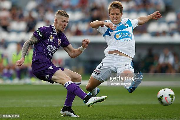 Andy Keogh of Perth Glory scores a Adrian Leijer of Melbourne Victory tries to defend during the round 14 ALeague match between the Melbourne Victory...