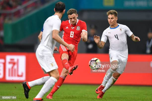 Andy King center of Wales national football team kicks the ball to make a pass against players of Uruguay national football team in their final match...