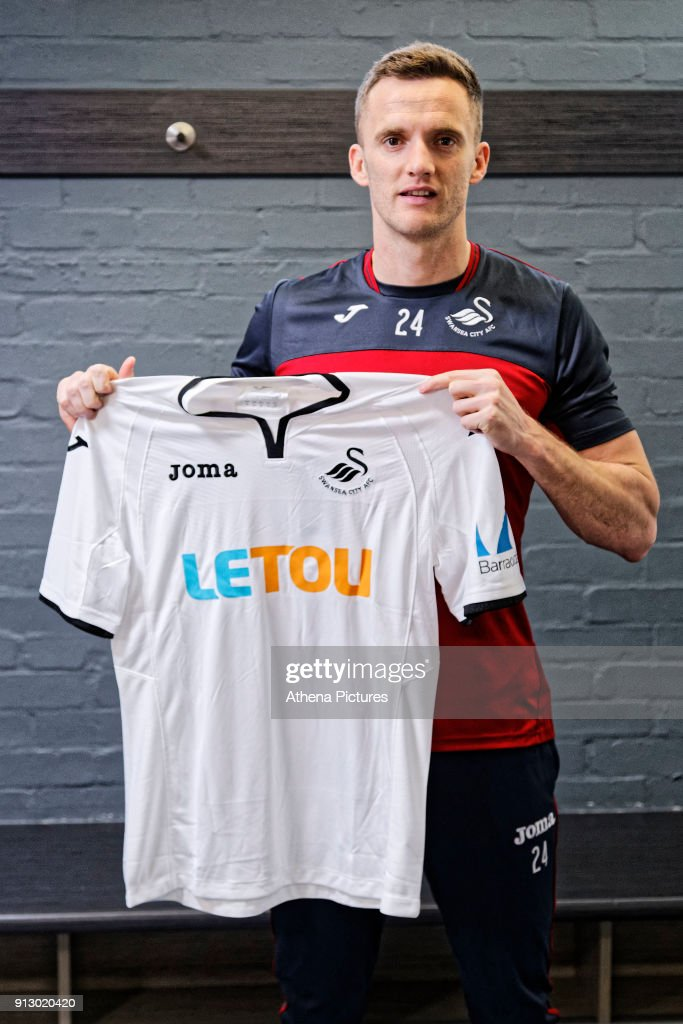 Andy King holds a home shirt as he is unveiled as a new Swansea City signing at The Fairwood Training Ground on February 01, 2018 in Swansea, Wales.