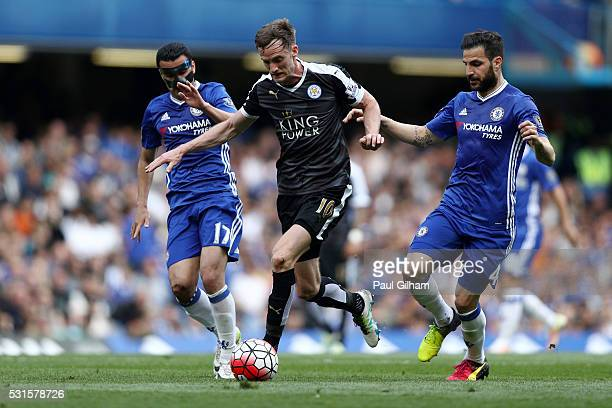 Andy King of Leicester City competes for the ball against Pedro and Sesc Fabregas of Chelsea during the Barclays Premier League match between Chelsea...
