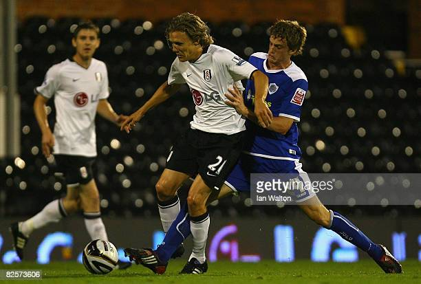 Andy King of Leicester City tries to tackle Jimmy Bullaed of Fulham during the Carling Cup second round match between Fulham and Leicester City at...