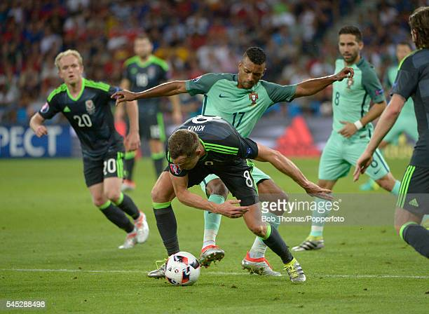 Andy King of Wales is tackled by Nani of Portugal during the UEFA EURO 2016 semi final match between Portugal and Wales at Stade des Lumieres on July...
