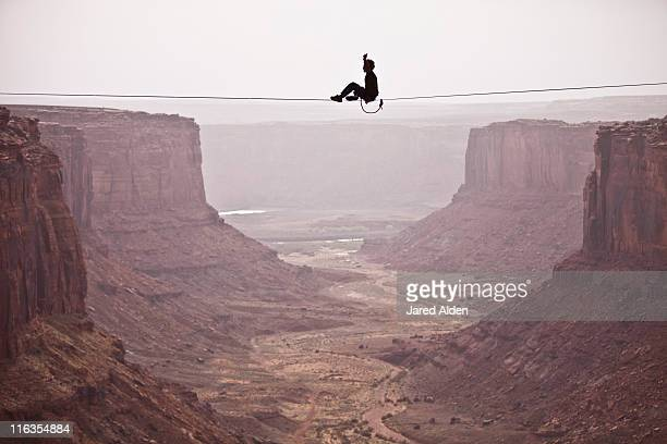 Andy Lewis working on a world record highline, three hundred and forty feet long, at the Fruit Bowl in Moab, Utah, USA.