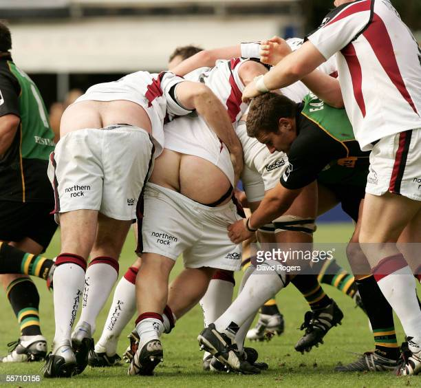 Andy Long and Micky Ward of Newcastle have their shorts pulled down by Mark Easter during the Guinness Premiership match between Northampton Saints...