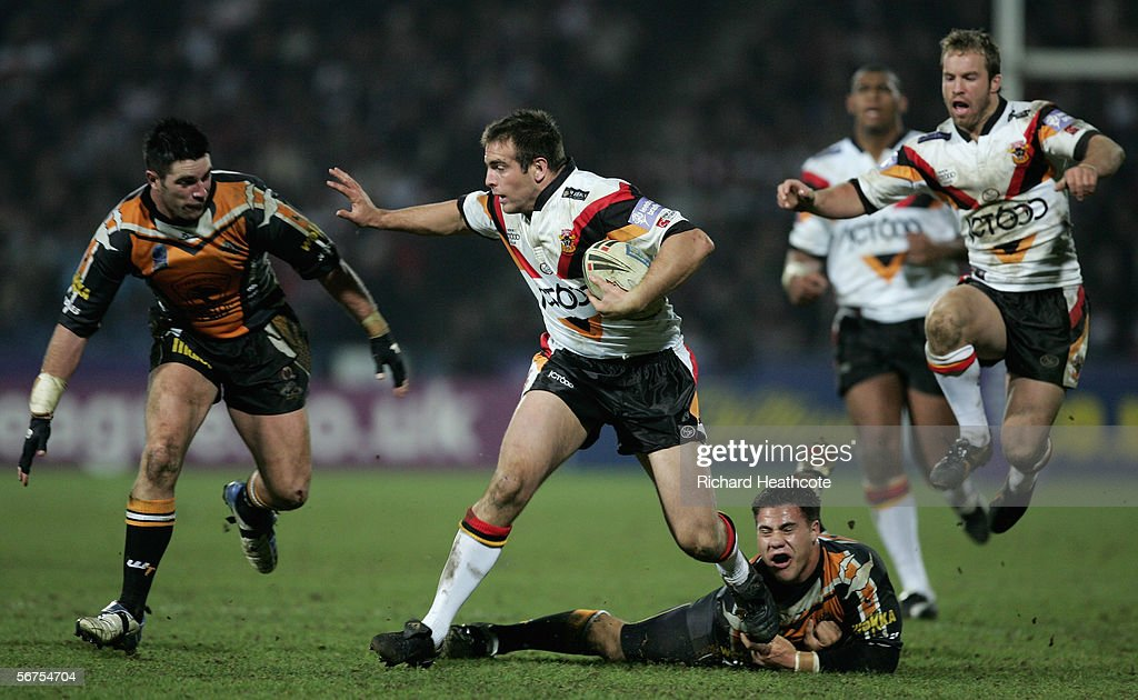 Andy Lynch of Bradford shakes off the tackle of Bronson Harrison (R) and the approaching challenge of Ryan O'Hara (L) of the Tigers during the Carnegie World Club Challenge between Bradford Bulls and Wests Tigers at the Galpharm Stadium on February 03, 2006 in Huddersfield, England