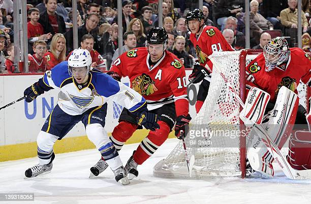 Andy McDonald of the St Louis Blues and Patrick Sharp of the Chicago Blackhawks skate around the net guarded by goalie Corey Crawford of the...