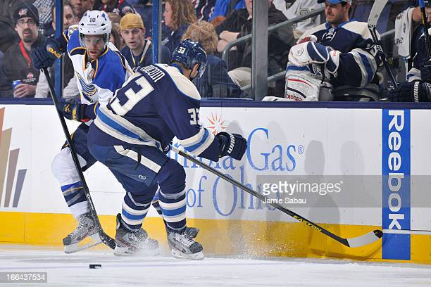 Andy McDonald of the St Louis Blues attempts to skate the puck around Adrian Aucoin of the Columbus Blue Jackets during the third period on April 12...