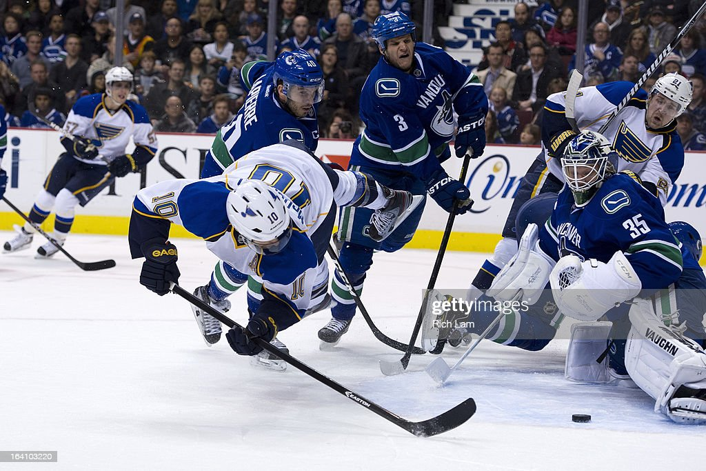 Andy McDonald #10 of the St. Louis Blues flies through the air while trying to put a shot past goalie Cory Schneider #35 of the Vancouver Canucks while Maxim Lapierre #40 and Kevin Bieksa #3 of the Vancouver Canucks and Patrik Berglund #21 of the St. Louis Blues look on during the first period in NHL action on March 19, 2013 at Rogers Arena in Vancouver, British Columbia, Canada.