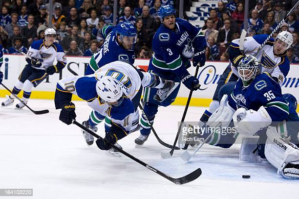 Andy McDonald of the St Louis Blues flies through the air while trying to put a shot past goalie Cory Schneider of the Vancouver Canucks while Maxim...