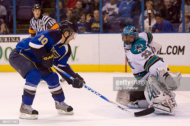 Andy McDonald of the St Louis Blues scores a goal against Brian Boucher of the San Jose Sharks at the Scottrade Center on March 12 2009 in St Louis...