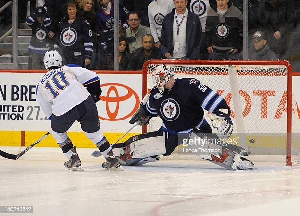 Andy McDonald of the St Louis Blues scores a goal against goaltender Chris Mason of the Winnipeg Jets during the shootout at the MTS Centre on...