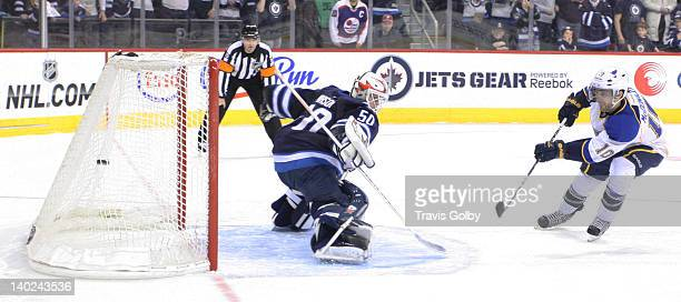 Andy McDonald of the St Louis Blues shoots the puck past goaltender Chris Mason of the Winnipeg Jets during the shootout at the MTS Centre on...